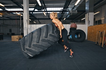Fit female athlete flipping a huge tire. Muscular young woman doing crossfit exercise at gym. Stock Photo
