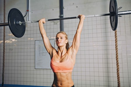 Beautiful strong young woman with barbell and weight plates overhead. Fit young female athlete lifting heavy weights. Caucasian female model performing crossfit exercise. Stock Photo