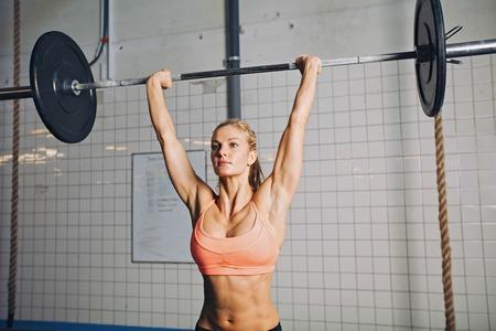 levantando pesas: Hermosa mujer joven y fuerte con la barra y placas de peso por encima. Hembra joven apta atleta levantar objetos pesados. Caucásica modelo femenino la realización de ejercicio crossfit.