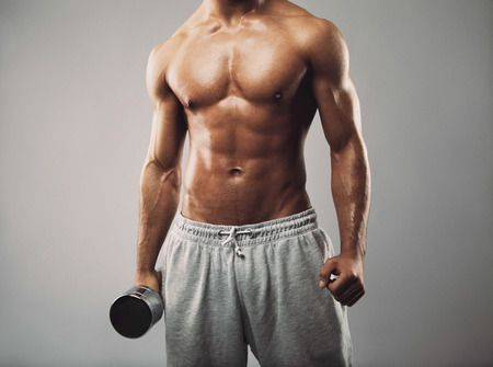 회색 배경에 아령을 들고 트레이닝 복 바지에 남성 모델의 스튜디오 샷. 벗은 근육질의 남자가 밖으로 작동합니다. 건강 및 피트니스 테마.
