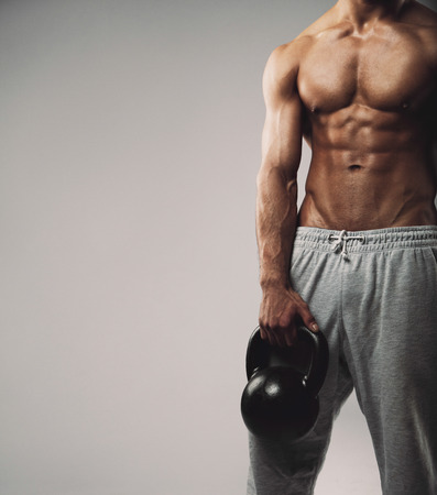 Cropped image of young man in sweatpants holding kettle bell. Crossfit workout theme on grey background work with empty copy space for your text. photo