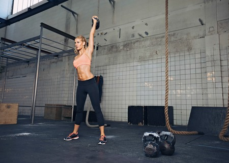 sport training: Young fitness woman lifting a heavy weight kettle bell at gym. Caucasian female athlete working out at gym. Fit young lady doing crossfit exercise.