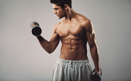 arms body: Hispanic young muscular man doing heavy dumbbell exercise for biceps. Fitness male model working out with dumbbells on grey background. Stock Photo
