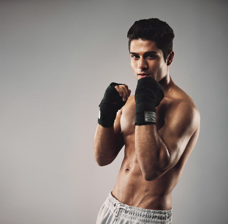 Portrait of fit young man wearing boxing gloves on grey background. shadow boxing workout concept.