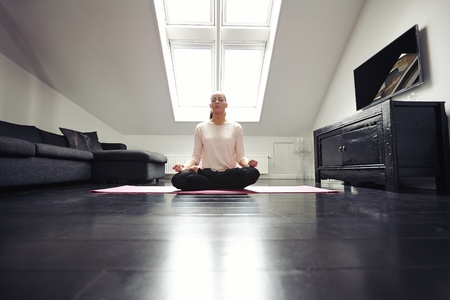 meditation room: Portrait of healthy young woman exercising yoga in living room. Fitness female relaxing with yoga meditation at home. Stock Photo