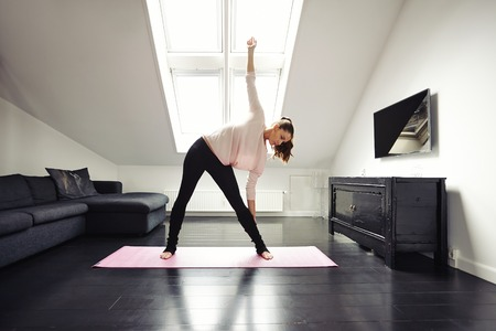 Fit young woman doing stretching exercise at her home. Healthy caucasian female model exercising in living room over exercise mat. photo