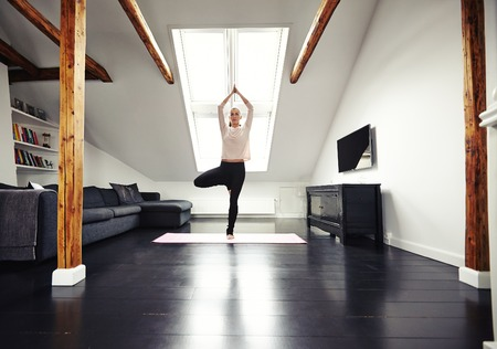 Full length image of young caucasian woman practicing yoga exercise at home. Fit young woman standing on one leg and meditating in her living room. photo