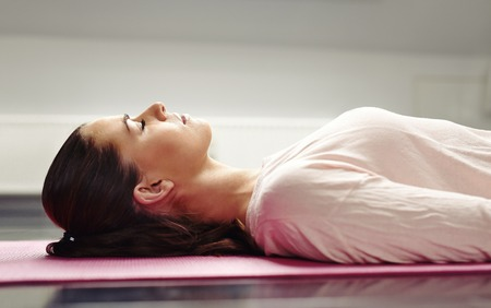 Close up image of young woman lying on a yoga mat with her eyes closed in meditation. Stock Photo