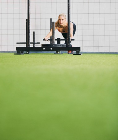 Strong young woman pushing the prowler on artificial grass turf Stock Photo