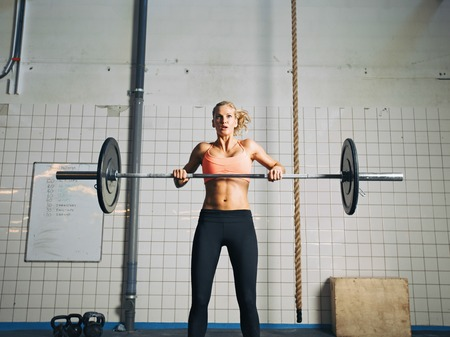 snatch: Fit female holding a barbell with weights for crossfit.