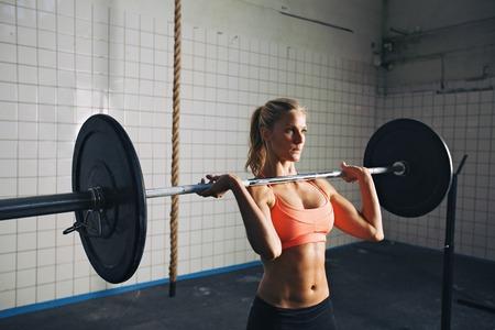 クロス フィット ジムでウェイト トレーニングを強い女性