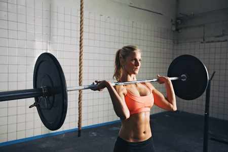 Strong woman lifting weights in cross-fit gym photo