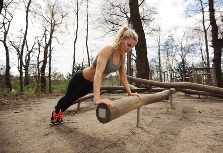 Strong and muscular young female doing pushups on a log.
