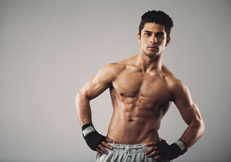 physique: Attractive young man with muscular physique posing on grey background Stock Photo