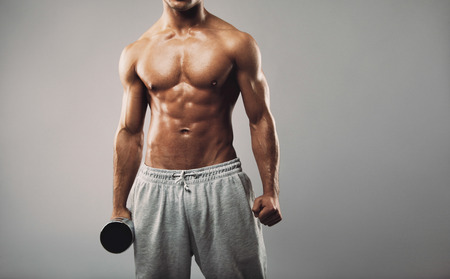 grey background: Cropped image of young muscular male fitness model wearing sweatpants holding a dumbbell against grey background Stock Photo