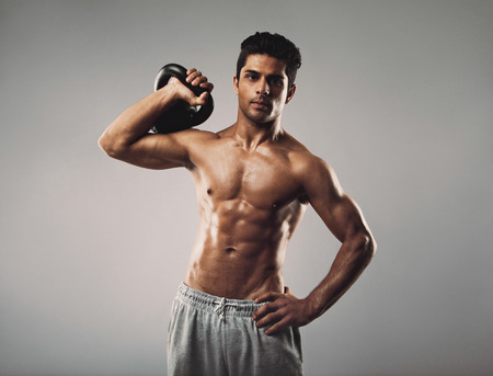 Hispanic fitness male model working out with kettlebell on grey background
