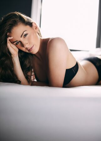 woman panties: Portrait of attractive young woman in lingerie lying on bed looking at camera Stock Photo
