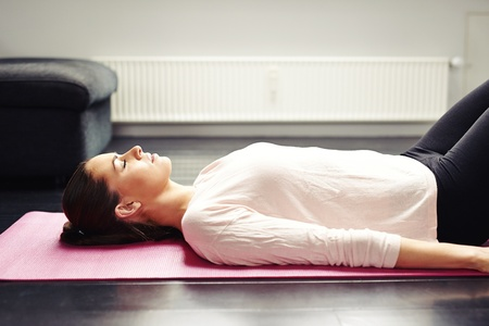 fit young woman relaxing on yoga mat photo