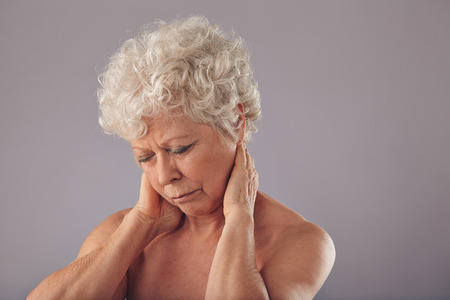 sore eye: Portrait of senior woman rubbing her sore neck against grey background