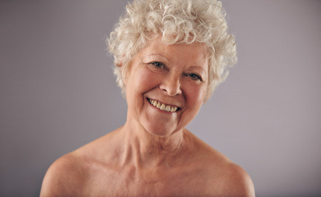 Headshot de una hermosa mujer madura aislado sobre fondo gris. Sin camisa caucásico edad sonriendo a la cámara femenino. Foto de archivo - 30408006