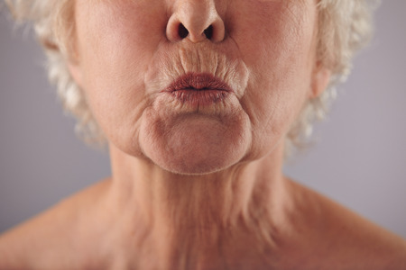 kissing lips: Close-up portrait of mature woman puckering lips against grey background Stock Photo