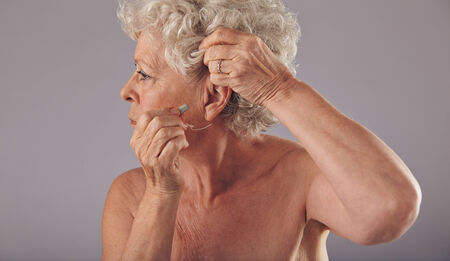 Side view portrait of a senior woman inserting a hearing aid in her ear against grey background Stock Photo
