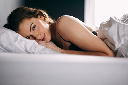 Portrait of pretty young woman lying in her bed looking at camera with a smile. photo
