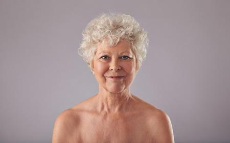 cuerpos desnudos: Retrato de la mujer hermosa sin camisa alto contra el fondo gris. Naked anciana sonriendo a la cámara. Foto de archivo