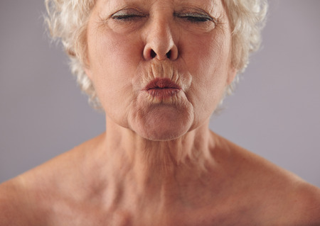 puckering: Cropped portrait of senior woman puckering lips. Mature female grimacing against grey background Stock Photo