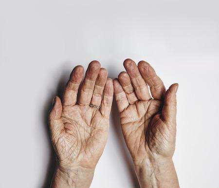 灰色の背景の空の女性両手の平面図です。年配の女性は、訴えかけるような手します。コピー スペースと高齢女性のしわのあるヤシの木.