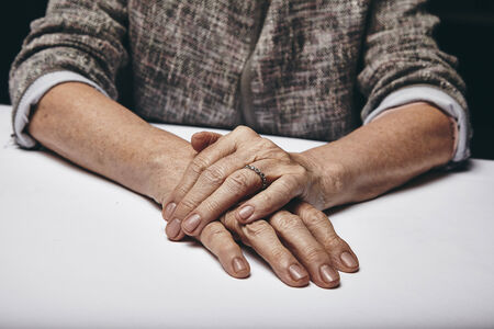cropped shots: Detail of old womans hands resting on grey surface. Senior females hand on top of another while sitting at a table. Stock Photo
