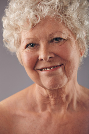 Headshot of attractive senior woman face with a sweet smile against grey background. Positive mature woman. photo