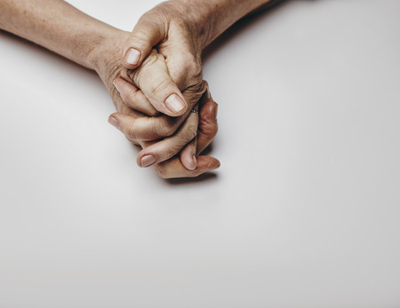 Senior womans hands isolated on grey background. Hands of a relaxed old female with copy space. Praying hands. photo