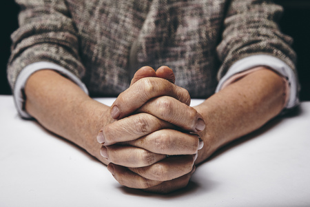 clasped: Studio photography of praying hands of a senior woman on table. Old hands clasped on a table.