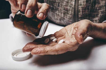 hand holding pills: Close-up image of senior woman taking out pills from the pills bottle. Focus on hands. Old female taking medicines.