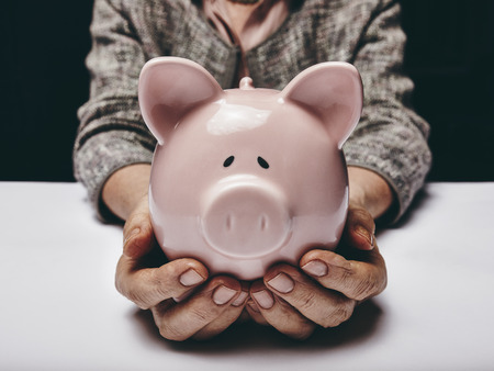 retirement homes: Close-up shot of elderly woman holding pink pig money-box. Senior woman hands holding a piggybank. Concept of saving money for old age. Stock Photo
