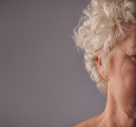 cropped: Cropped image of senior woman face with wrinkled skin on grey background. Crow feet on eyes of old woman. Stock Photo