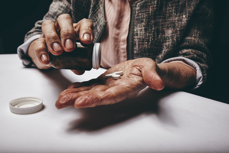 painkiller: Cropped shot of a old woman sitting at a table shaking a pill out of a pill bottle. Focus on hands. Senior female taking medicine.