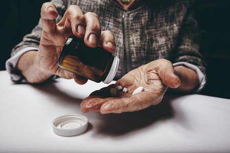 nutritional supplement: Cropped view of elderly woman taking prescription medicine from pill bottle. Senior females hands pouring pills on her palm while sitting at a table. Stock Photo