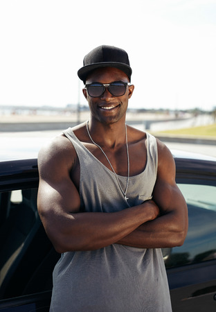 Portrait of handsome african guy with his arms crossed leaning against a car smiling. Stylised muscular guy wearing sunglasses and cap outdoors