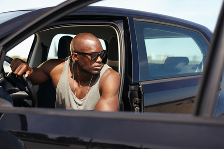 Image of handsome young man sitting in car looking away. Afro american male model sitting in car. Muscular man on road trip.  photo