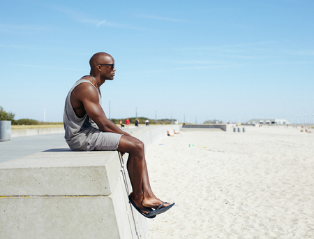Side view of young african man sitting on a beach promenade looking away. Afro american model relaxing outdoors at beach with copyspace.  photo