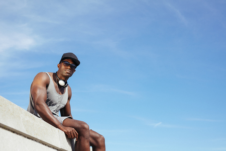 Stylish young african man sitting against blue sky. Man wearing sunglasses and cap with a headphone looking at camera.  photo