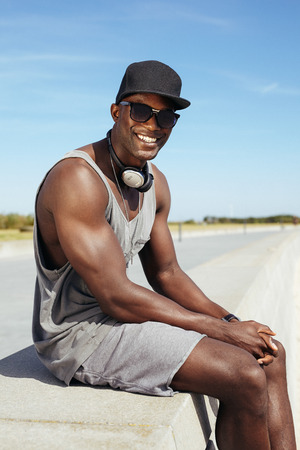 Portrait of happy young african man sitting on a promenade. Stylish male model wearing sunglasses and cap.   photo