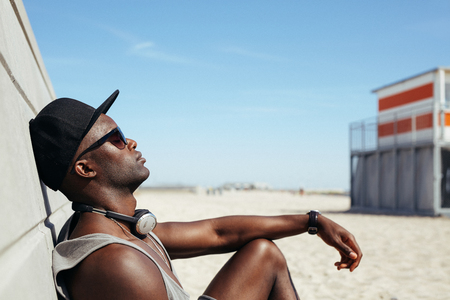 black  cap: Side view of relaxed african man leaning to a wall at beach sunbathing. Black guy wearing sunglasses and cap relaxing. Afro american male model resting outdoors