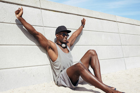 beach hunk: Muscular young man sitting by a wall stretching his hands smiling. African male model on beach.