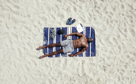 directly above: Top view of young man lying shirtless on a beach mat. African male model sunbathing.