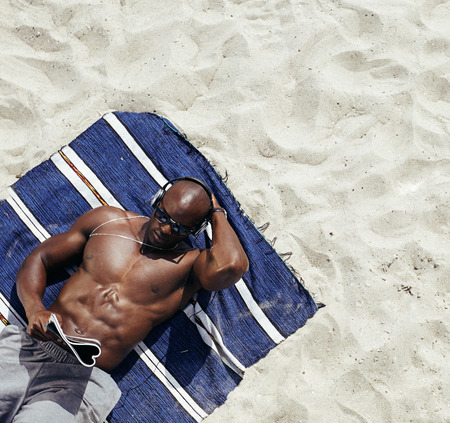 directly above: Image of muscular young man lying on a mat reading magazine. Shirtless male model relaxing on beach. Stock Photo