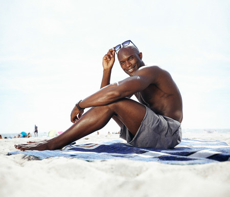 beach hunk: Portrait of handsome young man sitting on beach looking at camera smiling. Shirtless muscular man sunbathing on beach.