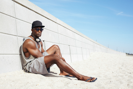 beach hunk: Handsome guy with headphones and sunglasses sitting on beach next to a wall. Muscular african american male model relaxing outdoors.